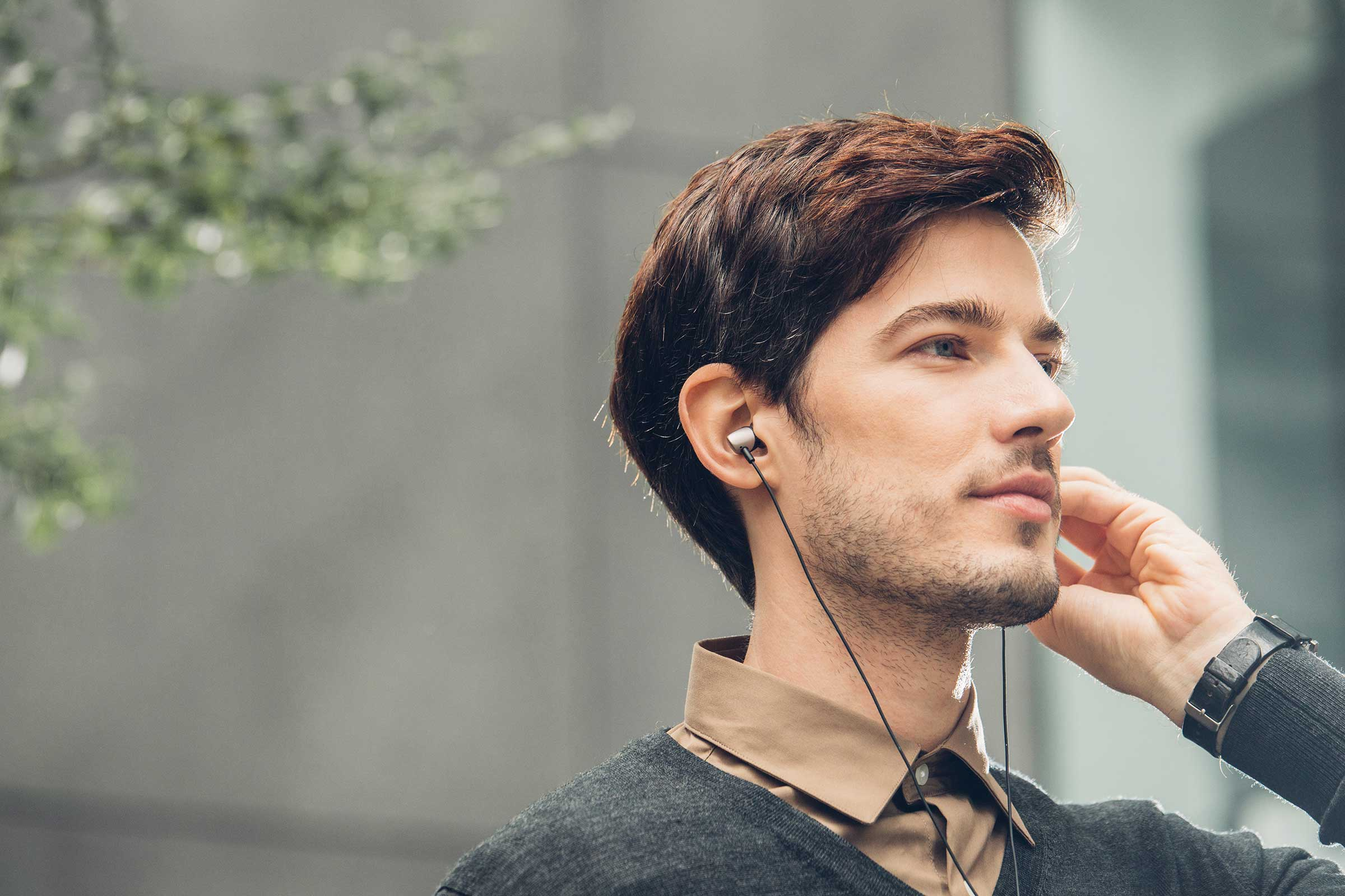 A male model listening to Moshi's Mythro headphones.