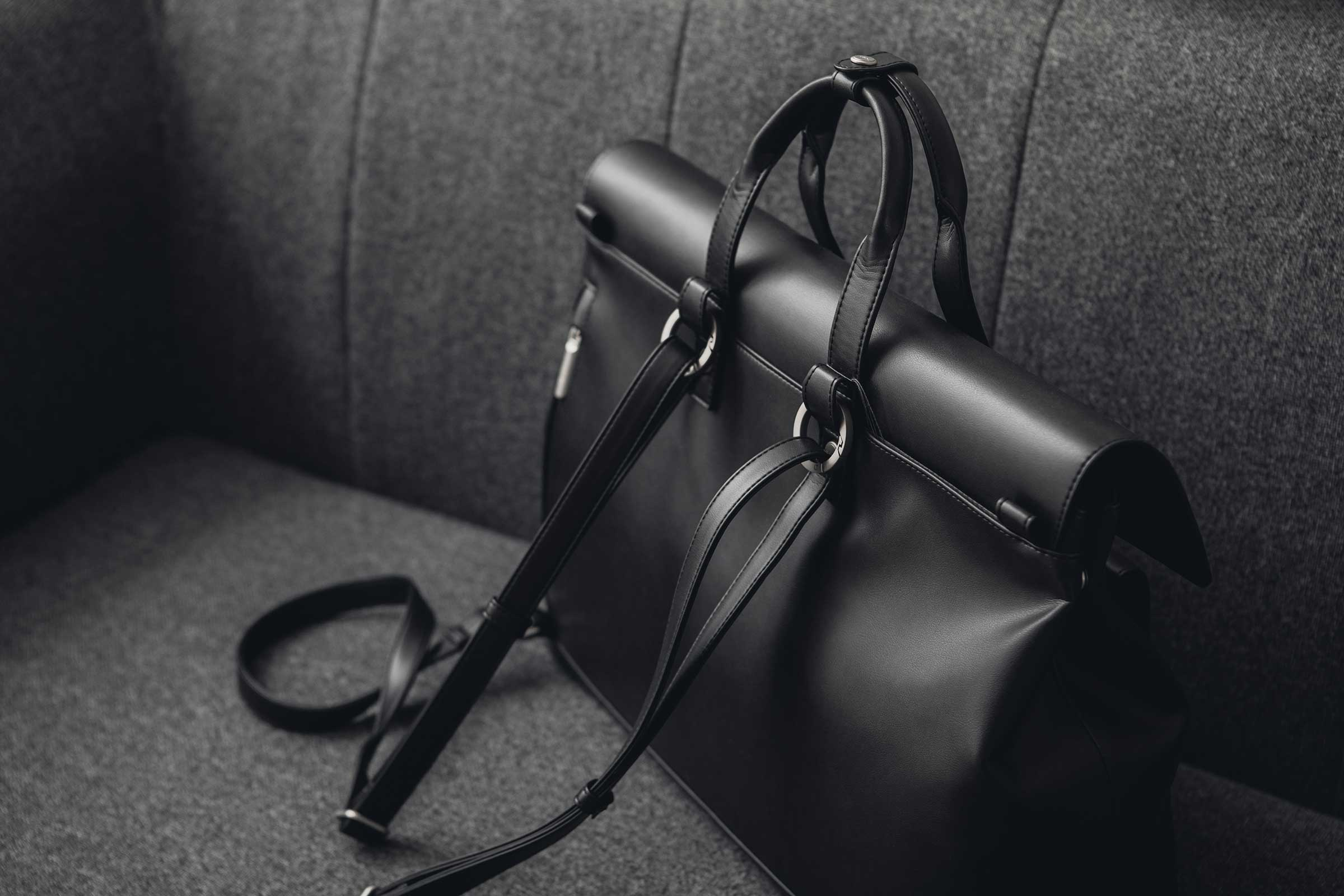 Moshi's Treya backpack made from vegan leather sitting on a stylish dark gray sofa.