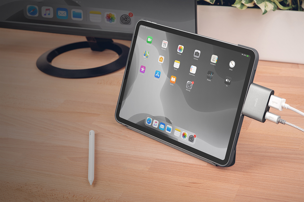 An iPad Pro charging and extending its content to an external display at the same time.