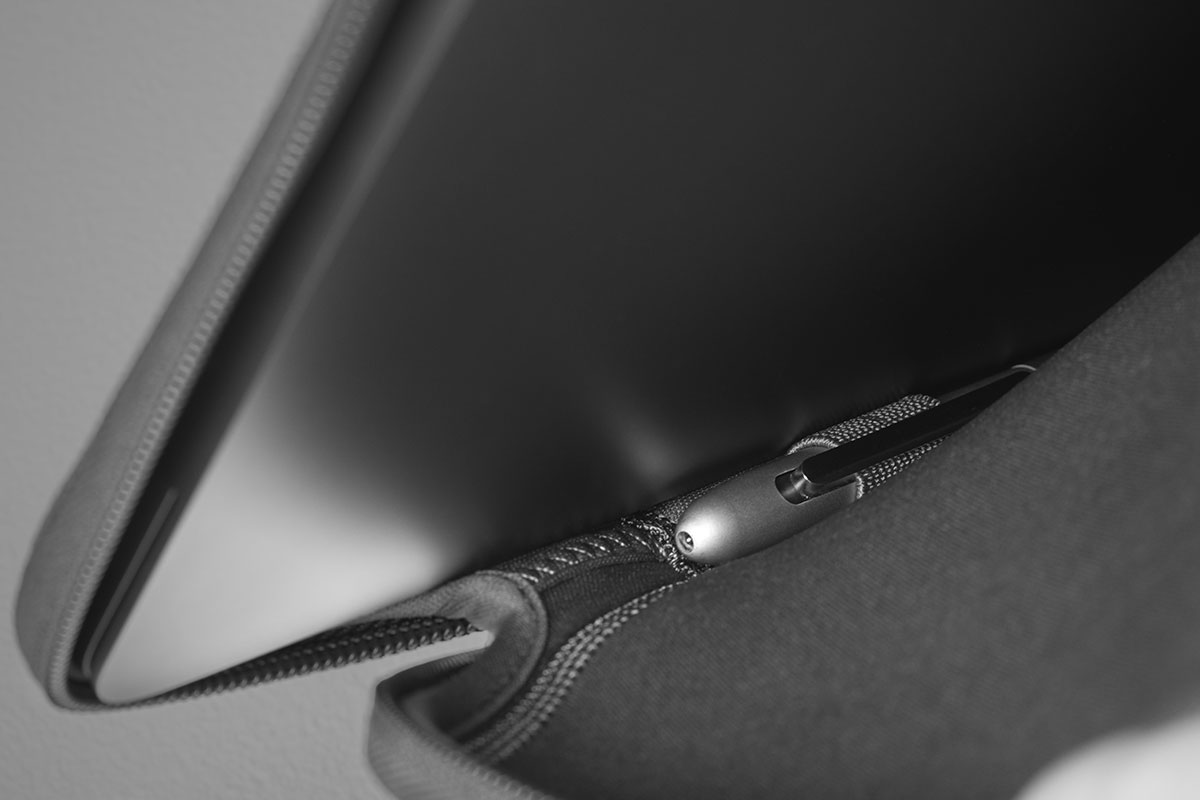 A close-up shot of a stylus attached to the pen loop inside the Pluma Laptop Sleeve for the 16-inch MacBook Pro.